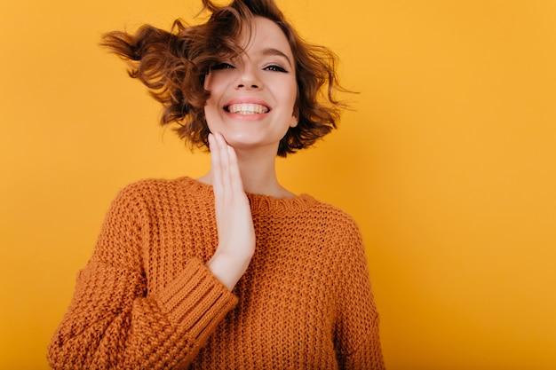 Binnenportret van gemakkelijke jonge vrouw die geluk uitdrukt