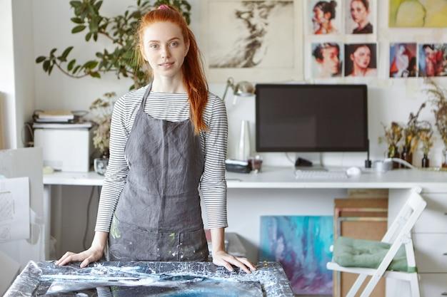 Binnenportret van getalenteerde jonge vrouwelijke schilder met gemberhaar gekleed in een grijze schort die zich geïnspireerd en gelukkig voelt tijdens het werken aan een foto met acrylverf