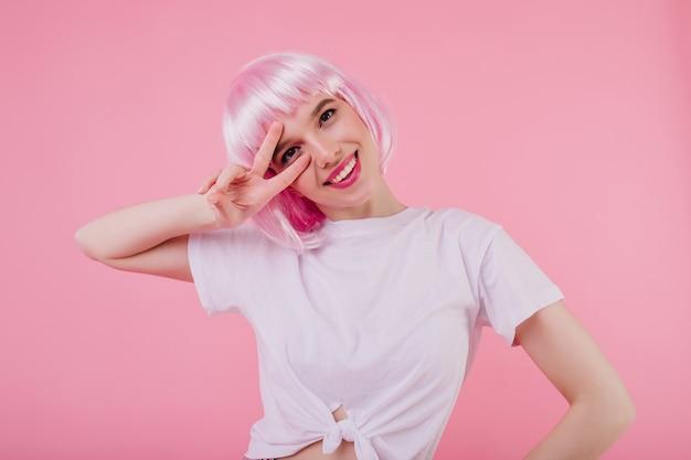 Binnenportret van glimlachend mooi meisje met roze haar dat op pastelkleurmuur wordt geïsoleerd. bevallige blanke dame in wit t-shirt poseren met vredesteken en lachen