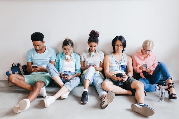Binnenportret van internationale studenten die wachten op onderzoek en hun telefoon gebruiken. jongens en meisjes die met gekruiste benen op de vloer zitten die apparaten in handen houden.