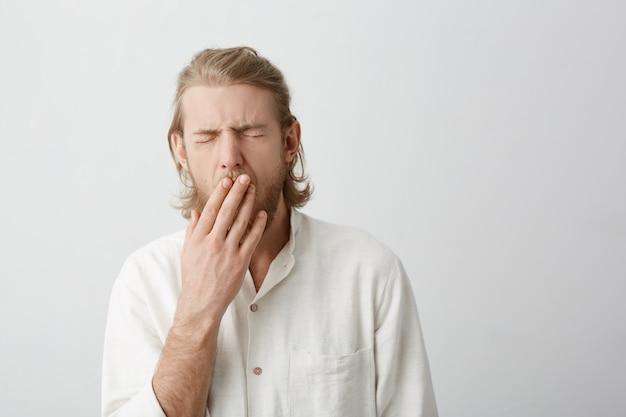Binnenportret van jong aantrekkelijk blond mannetje die en mond behandelen met handen geeuwen