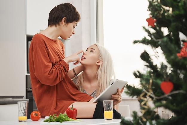 Binnenportret van jong sensueel en teder paar meisjes, die liefde en aantrekkingskracht uitdrukken terwijl het zitten in keuken en tablet op kerstmisochtend houden. samesex koppel flirt en eet ontbijt