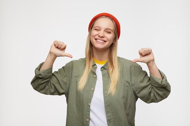 Binnenportret van jonge blije blanke vrouw die vrolijk op zichzelf wijst met opgeheven handen en knipoogt, geïsoleerd op blauw