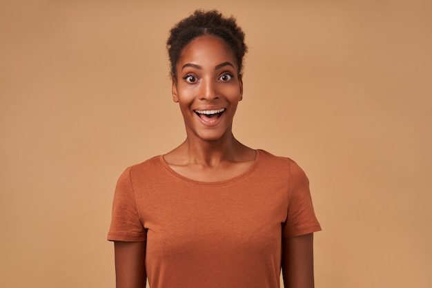 Binnenportret van jonge donkere dame met knotkapsel die opgewonden met grote ogen en geopende mond kijkt, geïsoleerd op beige