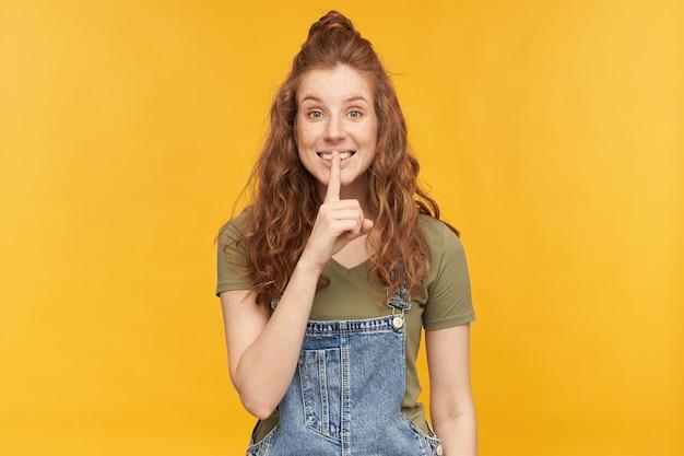 Binnenportret van jonge gembervrouw draagt blauwe denimoveralls en groen t-shirt glimlacht breed, flirt met iemand en toont stiltegebaar
