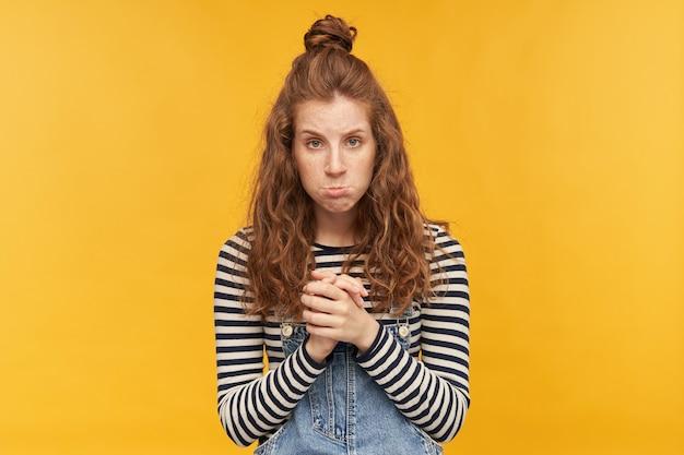 Binnenportret van jonge ontevreden gembermeisjes, houdt haar handpalmen bij elkaar, buigt haar lippen met een droevige gezichtsuitdrukking. geïsoleerd over gele muur