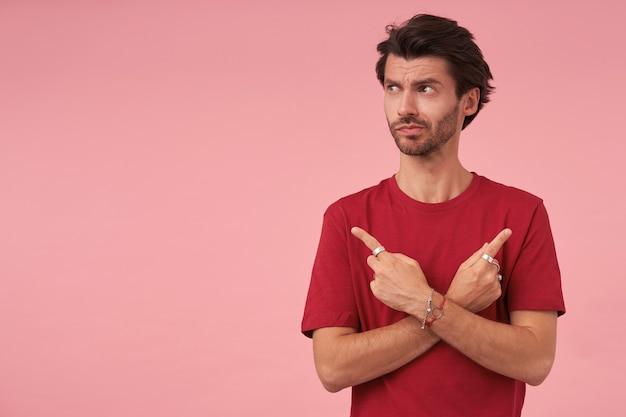 Binnenportret van knappe donkerharige jonge man die opzij kijkt met een twijfelend gezicht, met wijsvingers in verschillende kanten, terwijl hij poseren op roze