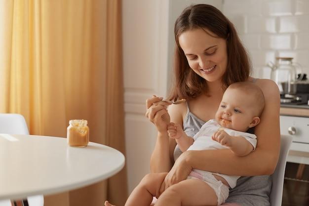 Binnenportret van moeder en kind zittend in de keuken aan tafel, vrouw met charmante glimlach die baby voedt met groente- of fruitpuree, aanvullende voeding van kind.
