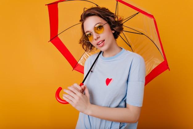 Binnenportret van mooi meisje in de blauwe parasol van de overhemdsholding. foto van prachtige blanke dame met krullend kapsel geïsoleerd op gele muur met paraplu.