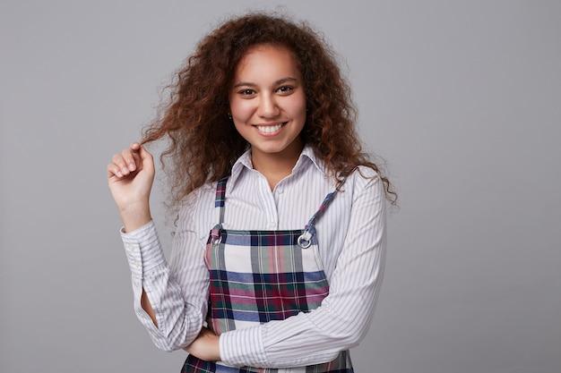 Binnenportret van mooie jonge donkerbruine vrouw die haar krullend haar met opgeheven hand trekt terwijl vrolijk kijkt, geïsoleerd op grijs