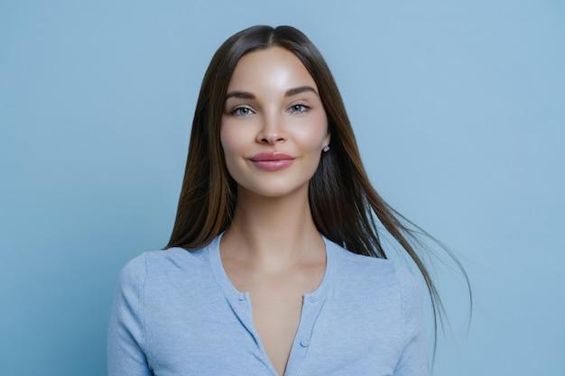 Binnenportret van mooie vrouw voelt zich overdag gelukkig en zorgeloos, heeft lang steil haar, draagt blauwe trui, geniet van positief gesprek, staat binnen