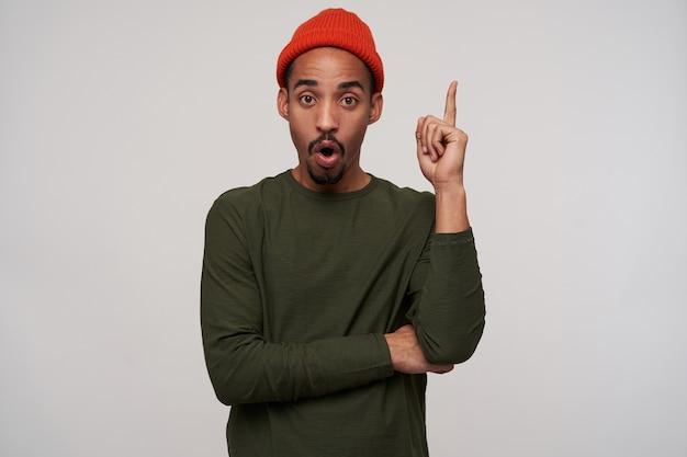 Binnenportret van opgewonden jonge donkerharige bebaarde man met donkere huid die zijn wijsvinger opheft en zijn mond rondt, geïsoleerd op wit