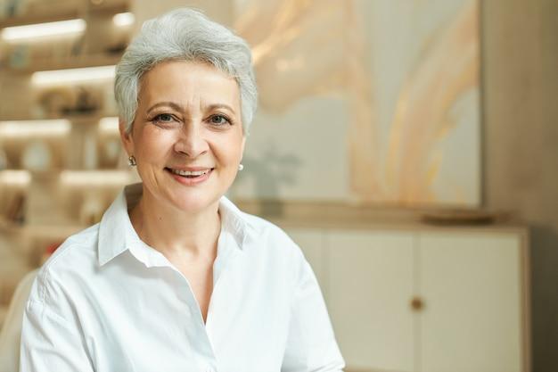 Binnenportret van succesvolle onderneemster van middelbare leeftijd met kort grijs haar die bij haar bureau werken