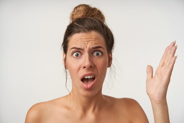 Binnenportret van verwarde jonge vrouw die op wit met opgeheven handpalm staat, fronsend met grote ogen en geopende mond