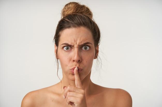 Binnenportret van vrij knorrige vrouw die wijsvinger naar haar lippen opheft, vraagt om stilte te houden, fronsend en serieus kijkend