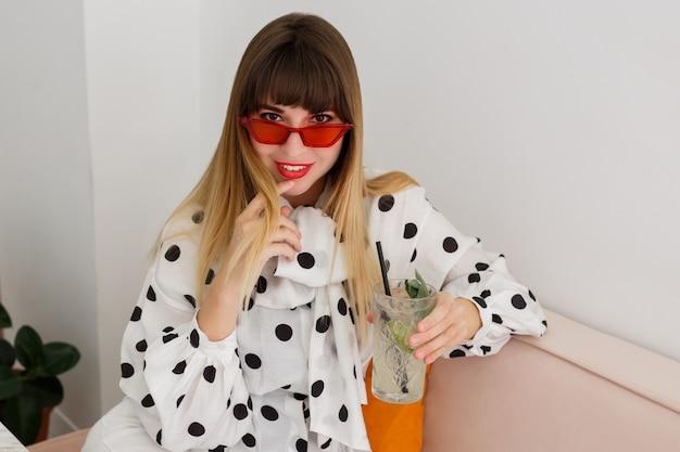 Binnenportret van vrij modieuze vrouw die in rode zonnebril drank in koffie drinken
