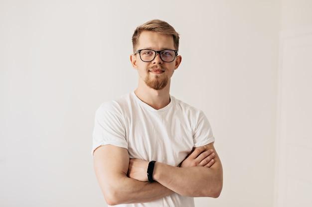 Binnenportret van zelfverzekerde jonge man in witte kleren poseren met charmante glimlach over geïsoleerde muur.