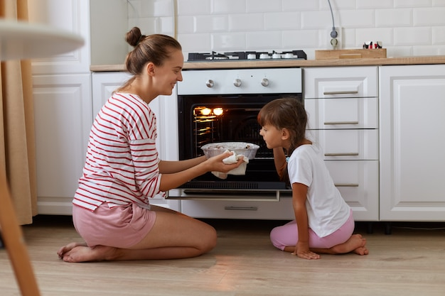 Binnenprofielfoto van lachend bakken uit de oven, haar dochter die in de buurt staat en heerlijke snoepjes ruikt, kind dat moeder helpt in de keuken, familie die thuis poseert terwijl ze op de grond zit.