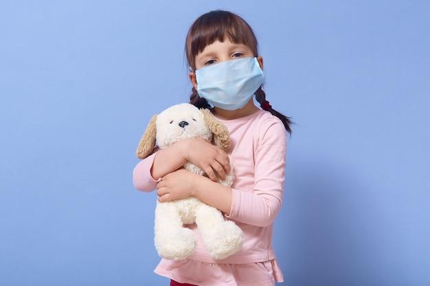 Binnenschot van aantrekkelijk kindmeisje dat beschermend geneeskundemasker draagt, dat puppystuk speelgoed in haar handen houdt, die vlechten heeft, het stellen
