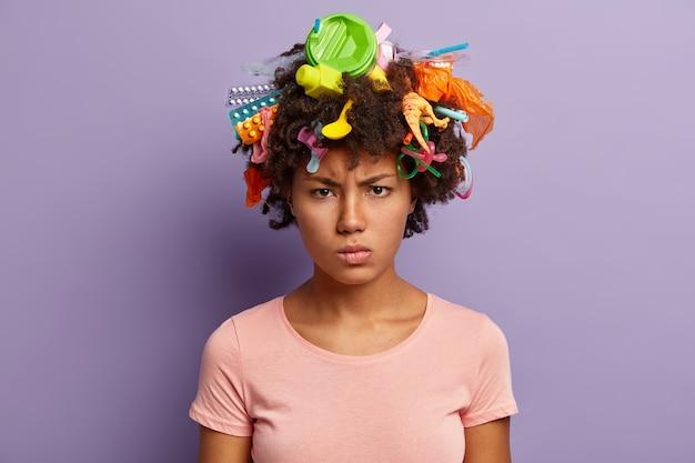 Binnenschot van boze gefrustreerde afro-amerikaanse vrouw met krullend kapsel, voelt zich ontevreden, geïrriteerd door de mensheid vanwege milieuvervuiling, betrokken bij vrijwilligerswerk bij het opruimen van onze natuur