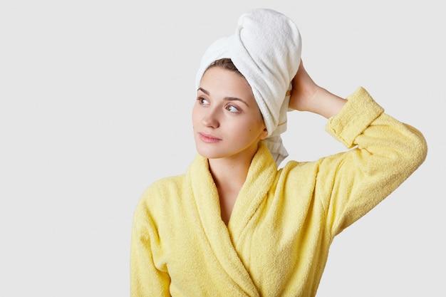Binnenschot van dromerige vrouw draagt badjas en handdoek, voelt zich ontspannen na het douchen, kijkt opzij met kopie ruimte op wit voor uw advertentie of promotionele inhoud