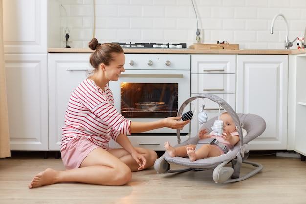 Binnenschot van een vrouw met een casual gestreept shirt zittend op de vloer in de keuken met haar peuterdochter in schommelstoel, vrouwelijke taart bakken of diner maken.