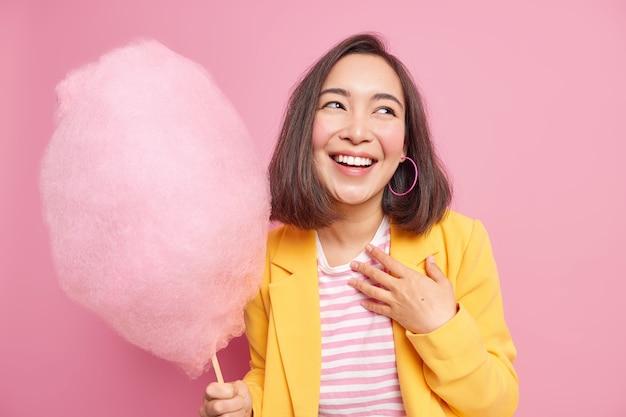 Binnenschot van gelukkige aziatische vrouw met donker haar glimlacht in grote lijnen herinnert zich iets grappigs geniet van vrije tijd houdt smakelijke zoete suikerspin opzij gericht draagt gele jas geïsoleerd op roze