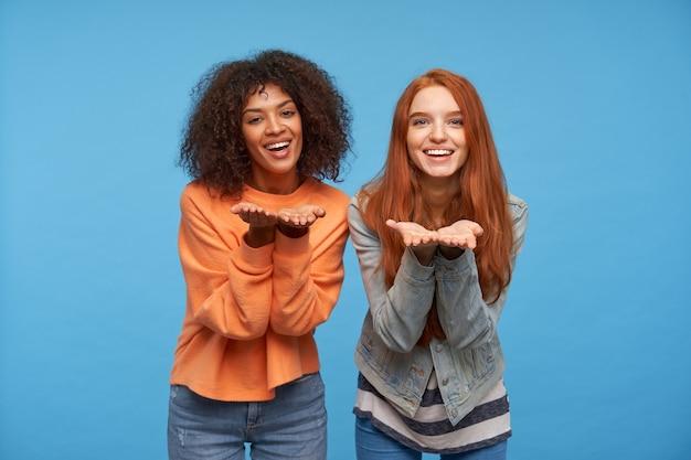 Binnenschot van gelukkige jonge aantrekkelijke vrouwen die positief met brede prettige glimlach kijken en opgeheven handen houden, geïsoleerd over blauwe muur