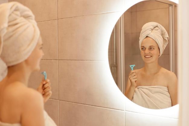 Binnenschot van gelukkige jonge volwassen vrouw met scheermes voor het scheren van de oksel in de hand, poseren in de badkamer voor ontharing, kijken naar spiegelreflectie, hygiëneprocedures.