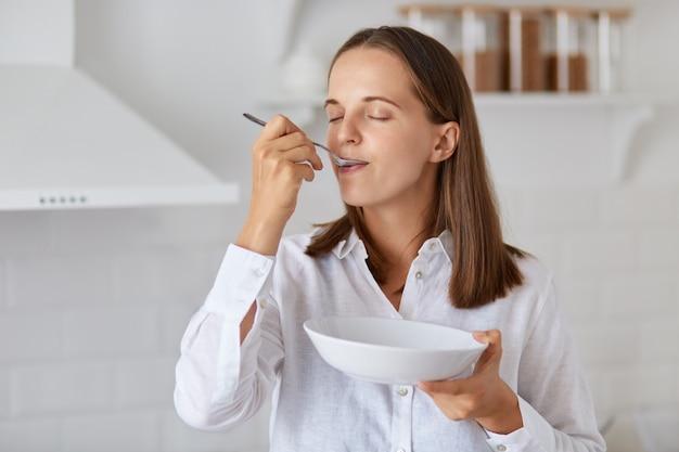 Binnenschot van gelukkige jonge vrouw die soep thuis eet. genieten van lekker ontbijt of diner, wit overhemd dragen, poseren met lichte keuken op de achtergrond.