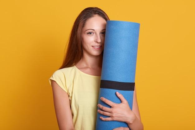 Binnenschot van jonge mooie vrouwenatleet die t-shirttribunes dragen die blauwe geschiktheidsmat houden