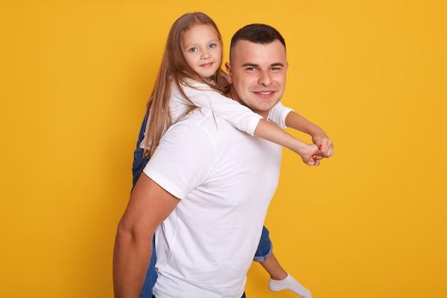 Binnenschot van knappe vaderholding op terug aanbiddelijk peuterjong geitje, mens en zijn kind stellen geïsoleerd over gele muur. speelse familie plezier, concept van liefdevolle familie vrijetijdsactiviteiten.