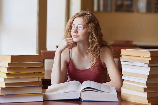 Binnenschot van krullend haired mooi meisje die oprecht glimlachen, uit venster kijken, boek openen, haar hand dicht bij gezicht plaatsen, boeken op bureau hebben, vrijetijdskleding dragen, zittend in klaslokaal.