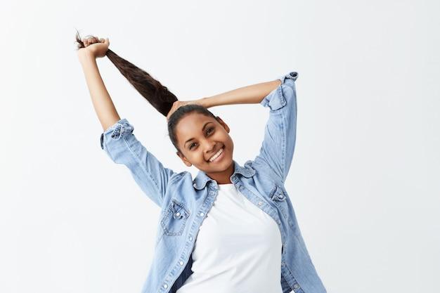 Binnenschot van mooi afro-amerikaans meisje met lang zwart haar verzameld in paardenstaart gekleed terloops gekleed binnenshuis poseren, haar kapsel aanpassen voordat ze uitgaat. mensen en emoties concept.