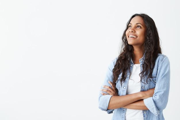 Binnenschot van mooie gelukkige afro-amerikaanse vrouwelijke werknemer status geïsoleerd op wit die vrolijk glimlachen, haar armen gevouwen houden, binnen ontspannen na het werk.