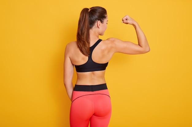 Binnenschot van mooie sterke spiervrouw die haar bicepsen en wapenspieren buigen, sportief wijfje die blak bovenkant en rode leggins dragen, het model stellen na het uitwerken. gezonde levensstijl en sport concept.
