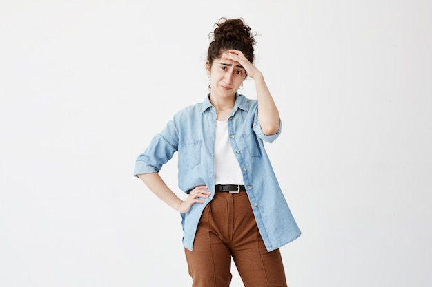 Binnenschot van ongelukkige jonge vrouw die lijden aan slechte hoofdpijn of migraine na een zware werkdag, met een pijnlijke blik, met de hand op het voorhoofd. negatieve menselijke emoties en gevoelens.