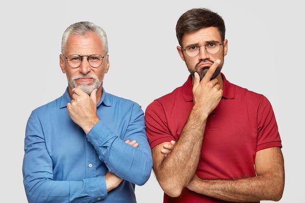 Binnenschot van twee partners van verschillende leeftijd, kin vasthouden en kijken met ontevreden uitdrukkingen, kan geen oplossing van probleem vinden, naast elkaar staan, geïsoleerd over witte muur. emoties concept