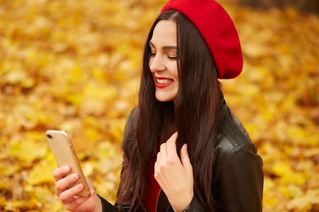 Binnenschot van vrouw die selfie via mobiele telefoon in herfst nemen. de herfstmeisje die smartphone videogesprek hebben.