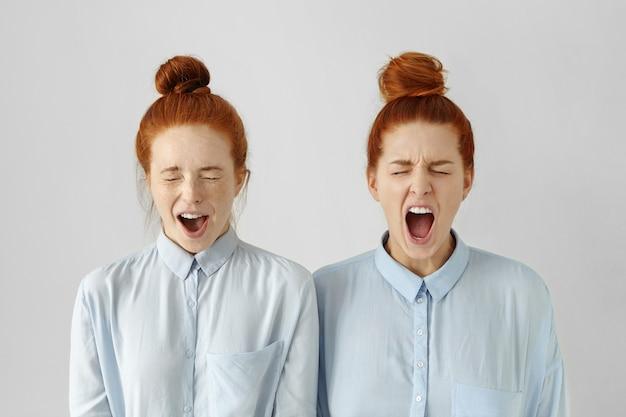 Binnenschot van woedende jonge europese vrouwen die identieke kapsels en formele kleding dragen