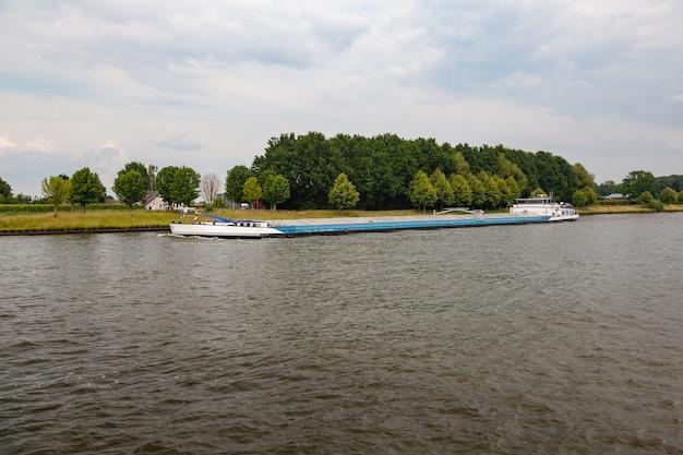 Binnenvaartschip onder een bewolkte hemel in nederland
