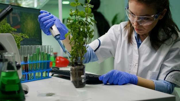 Biochemicus die wetenschappelijk groene vloeistof neemt met micropieptte puttin op jonge boom die genetische mutatie typt en biochemie-expertise op de computer typt. bioloogvrouw die in biochemisch laboratorium werkt