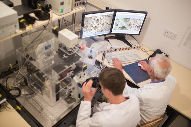 Biochemicus en student die microscopische beelden op computer bekijken