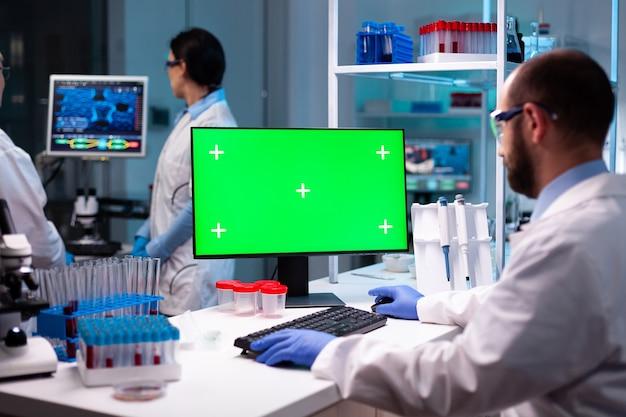 Biochemicus werkt in laboratorium met behulp van groene mock-up scherm chroma key