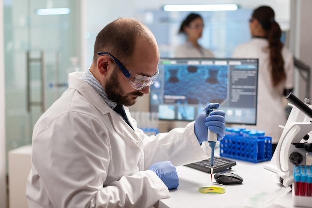 Biochemie-gezondheidszorgwetenschapper die bloedmonster test met behulp van micropipet