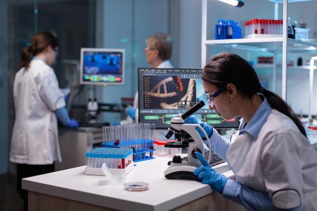 Biochemische wetenschappers die de reactie van het virus op de microscoop in het laboratorium bestuderen studying