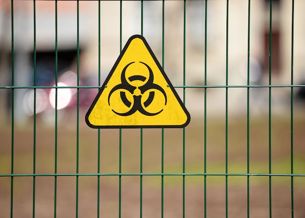Biohazardwaarschuwingsbord op de groene decoratieve omheining van de metaaldraad