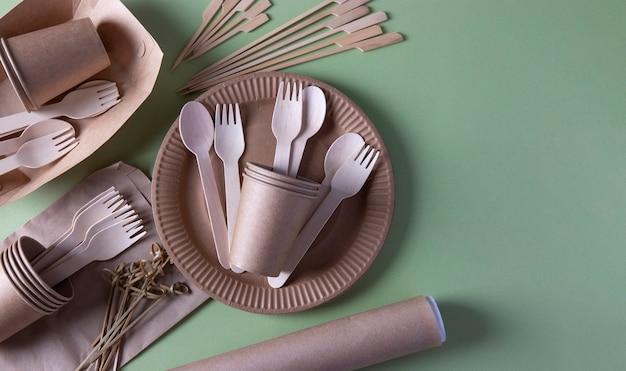 Biologisch afbreekbaar wegwerpservies op ambachtelijke papieren borden - vorken, lepels, glazen, perkament, houten en bamboespiesen. zero waste. ruimte voor tekst