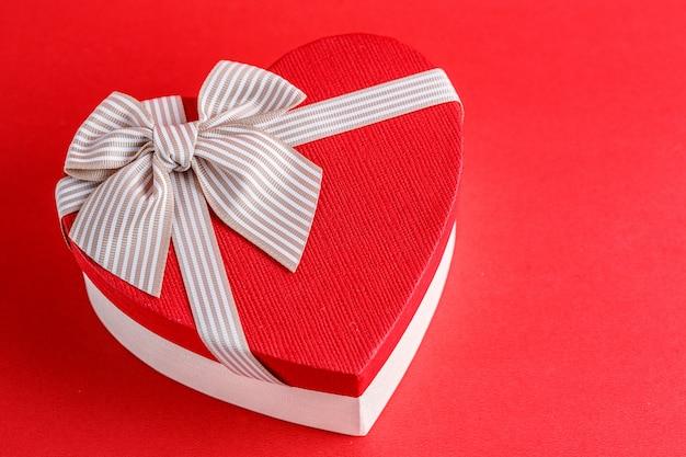 Biologisch afbreekbare kartonnen geschenkdoos in de vorm van een hart met linten op rood