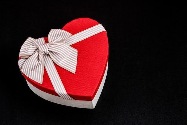 Biologisch afbreekbare kartonnen geschenkdoos in de vorm van een hart met linten op zwart